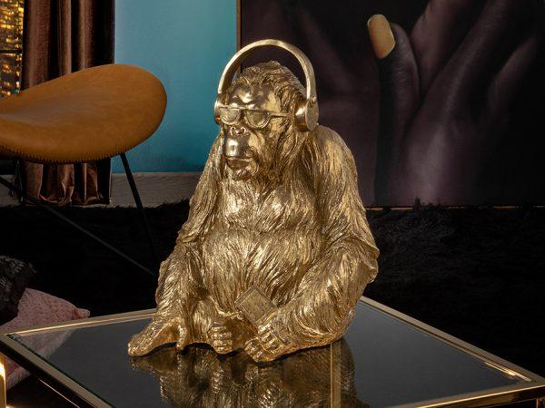 Figura mediana de orangután con cascos musicales y gafas. Realizada en poliresina, acabado en PAN DE ORO.